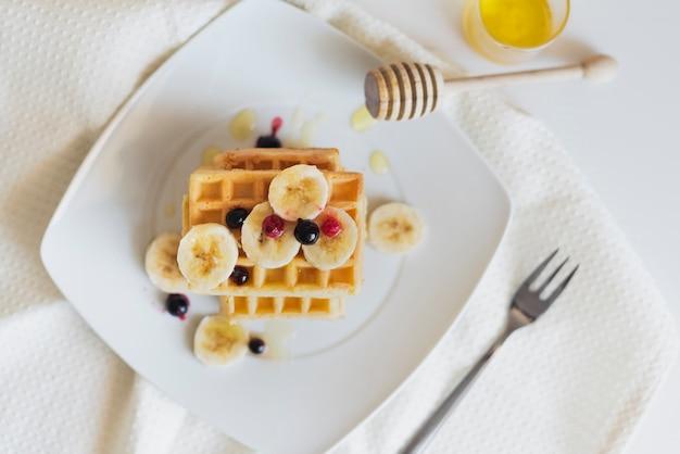 Flache lage von waffeln mit früchten und honig Kostenlose Fotos