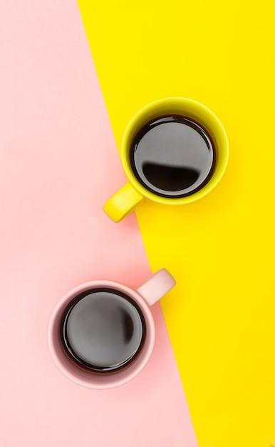 Flache lage von zwei kaffeetassen mit rosa und gelb Premium Fotos