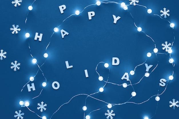 Flache lage weihnachtsfeiertagsfeier des neuen jahres oder des weihnachtsmusters dekorative papierschneeflocken und girlande von festlichen lichtern auf blauem papier. modischer c; assic blauer einfarbiger getonter hintergrund. Premium Fotos