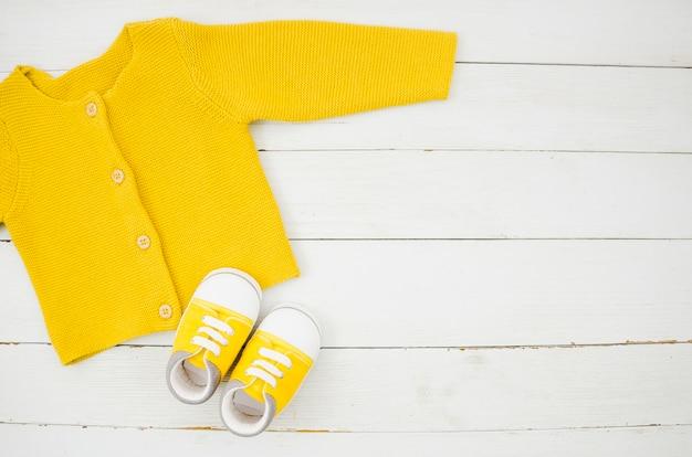 Flache lagebabykleidung mit hölzernem hintergrund Premium Fotos