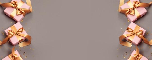 Flache lagezusammensetzung mit den schönen geschenken eingewickelt im festlichen papier- und goldbandbogen auf grau Premium Fotos