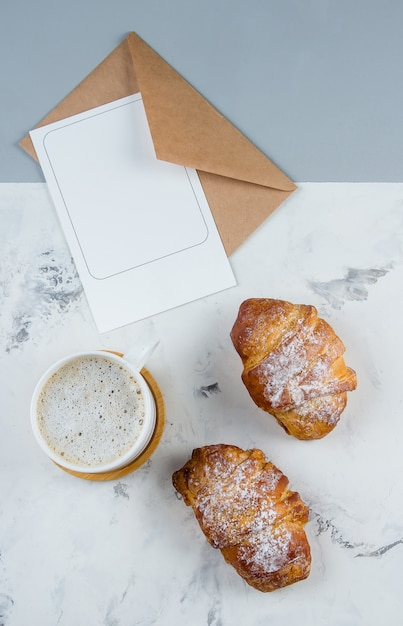 Flache lagezusammensetzung mit tasse kaffee, hörnchen und sauberer leerer anmerkung für text auf hintergrund. Premium Fotos