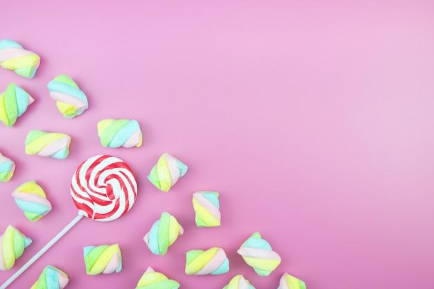 Flache laien süß candy lollipop marshmallow bunter rosa hintergrund Premium Fotos