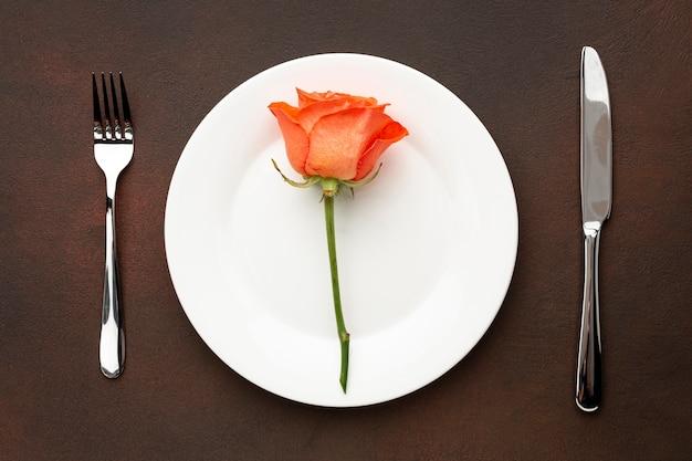 Flache laienanordnung für valentinstagabendessen mit orangenrose Kostenlose Fotos