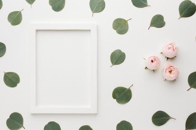 Flache laienblätter und -rosen mit kopienraumrahmen Kostenlose Fotos