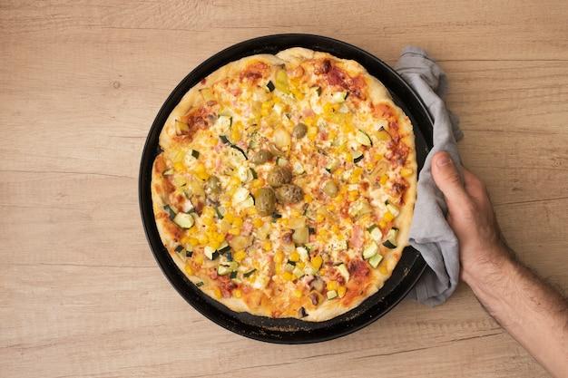 Flache laienhand, die pfanne mit gekochter pizza hält Kostenlose Fotos