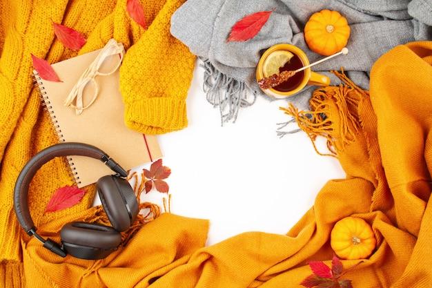 Flache laienherbstzusammensetzung mit herbstlaub, heißer tasse tee und einem warmen wollorangenpullover Premium Fotos
