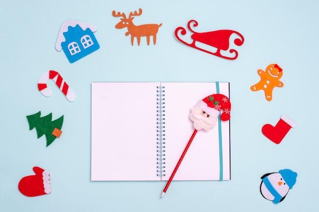 Flache laienkomposition mit leerem offenem notizbuchstift mit weihnachtsmann und weihnachtsspielzeughandschuhpinguintannenbaumhaushirschschlitten-lebkuchensocke Premium Fotos