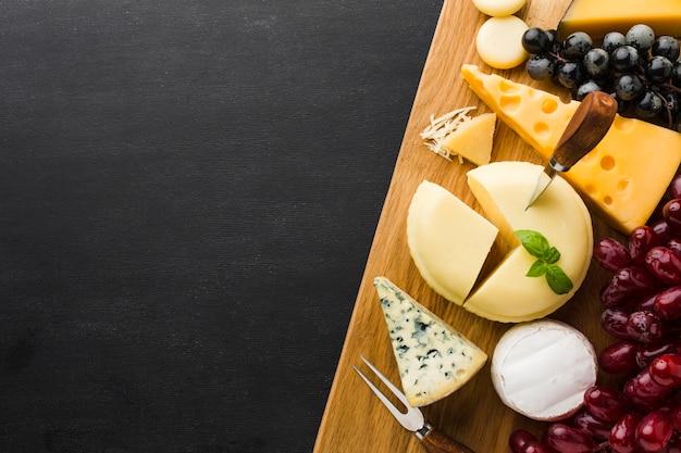 Flache laienmischung des feinschmeckerischen käses und der trauben auf schneidebrett mit kopienraum Kostenlose Fotos