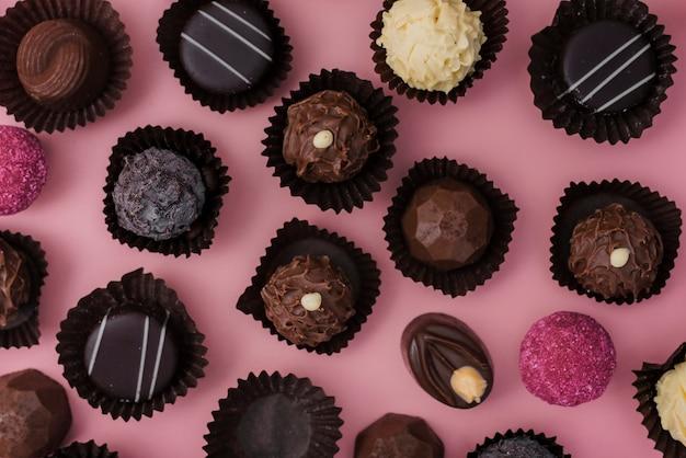 Flache laienmischung von schokoladen auf rosa hintergrund Premium Fotos