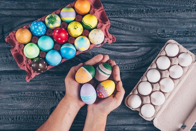 Flache legen ostereier im eierkarikatur mit den händen des mannes voller eier auf dunklem hölzernem hintergrund. Kostenlose Fotos
