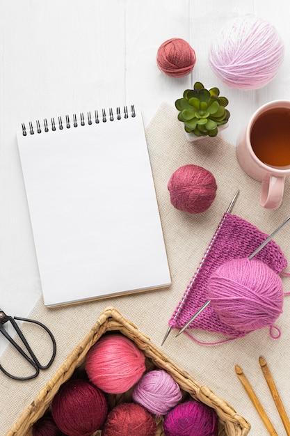 Flache strickgarnitur mit notizbuch und garn Premium Fotos