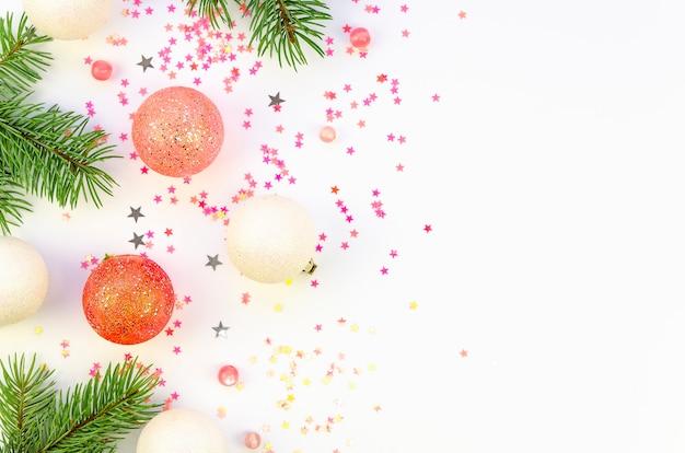 Flache tannenzweige mit weihnachtsdekorationen und konfetti auf weißem hintergrund Premium Fotos