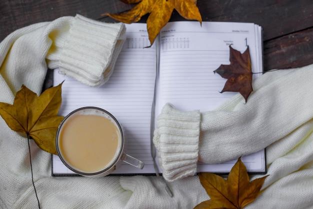 Flache zusammensetzung des herbstlaubs mit warmem pullover und tasse kaffee. Premium Fotos