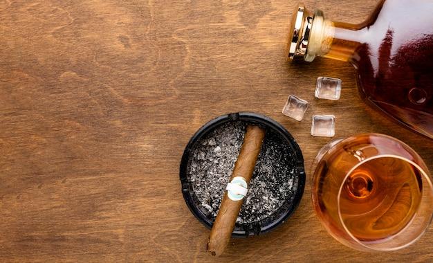 Flacher cognac und zigarre mit platz zum kopieren Kostenlose Fotos