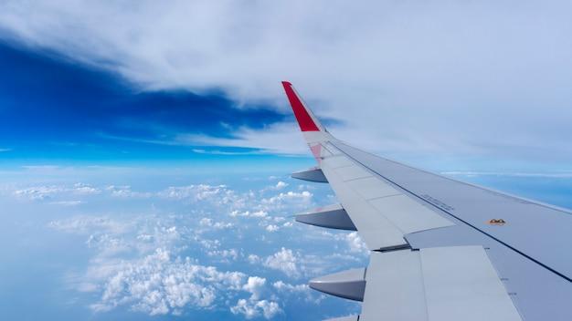 Flacher flügel auf dem blauen himmel und den wolken, kann für den luftverkehr zum reisen genutzt werden Premium Fotos