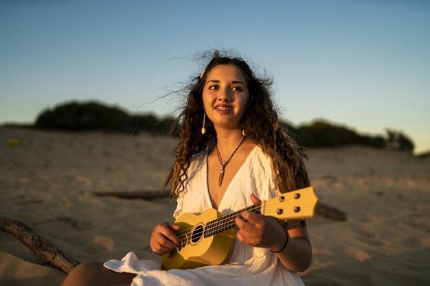 Flacher fokusschuss einer lächelnden frau, die eine gelbe ukulele am strand spielt Kostenlose Fotos