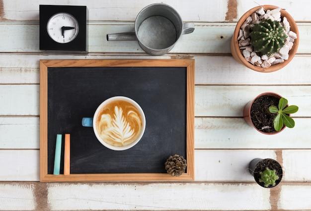 Flacher gartenschreibtisch mit tafel, uhr, kaktuspflanzen und kaffeetasse auf vintage-holz, flacher laien Premium Fotos