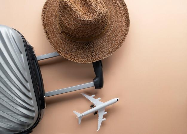 Flacher grauer koffer mit braunem hut und miniflugzeug Premium Fotos