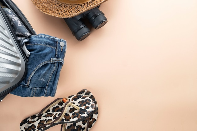 Flacher grauer koffer mit fernglas, hut, jeans und sandelholz. reise-konzept Premium Fotos
