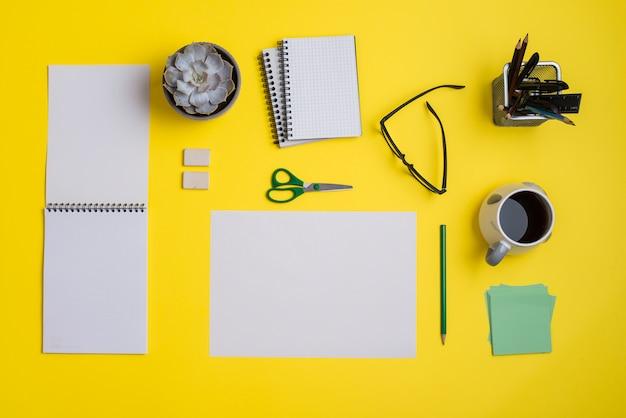 Flacher lagegeschäftsarbeitsplatz mit büroartikel und kaffee auf gelbem hintergrund Kostenlose Fotos