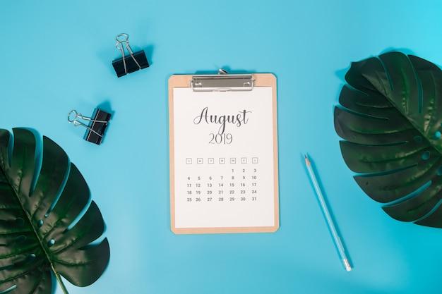 Flacher lagekalender mit klemmbrett, palmblättern und bleistift auf blauem hintergrund Premium Fotos