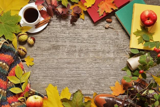 Flacher lagerahmen von roten, grünen und gelben blättern, von eicheln und von äpfeln des herbstes auf einem hölzernen hintergrund der weinlese. Premium Fotos