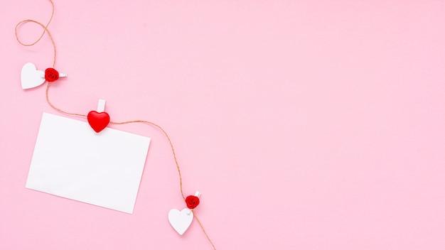 Flacher laienrahmen mit blatt papier und rosa hintergrund Premium Fotos