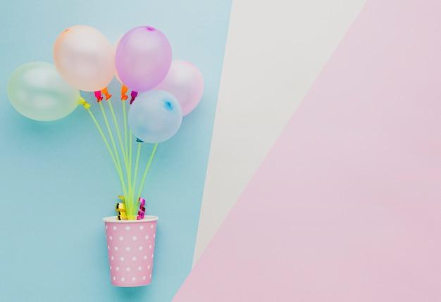 Flacher laienrahmen mit bunten ballonen und schale Kostenlose Fotos