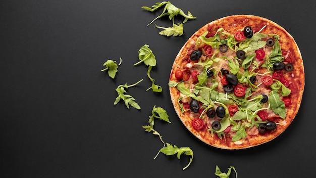 Flacher laienrahmen mit pizza und schwarzem hintergrund Kostenlose Fotos