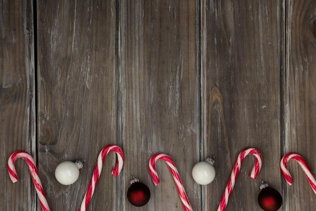 Flacher laienrahmen mit weihnachtskugeln und -süßigkeit Kostenlose Fotos
