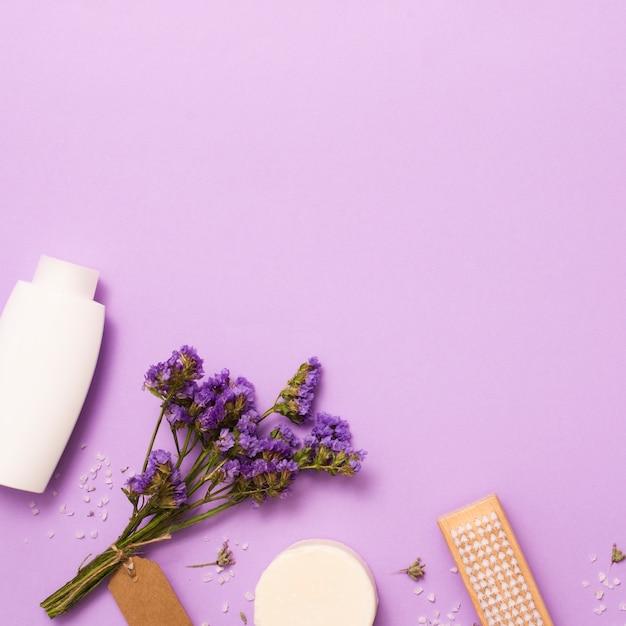 Flacher laienrahmen mit weißer flasche und lila blume Kostenlose Fotos