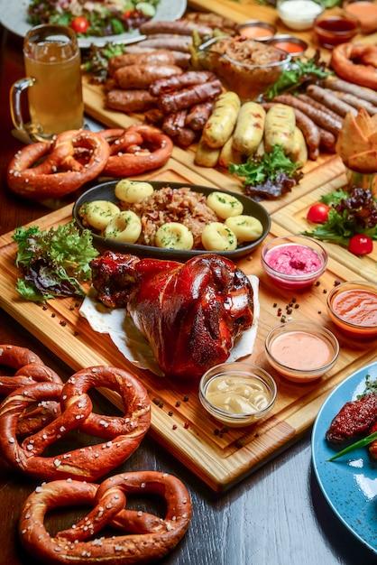 Flacher oktoberfest-esstisch mit gegrillten fleischwürsten, brezelgebäck, kartoffeln, gurkensalat, saucen, bieren Premium Fotos