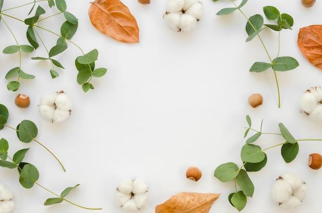 Flacher runder rahmen mit blättern und baumwollblüten Kostenlose Fotos