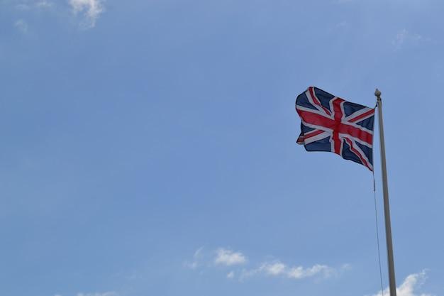 Flacher winkelschuss der flagge von großbritannien auf einer stange unter dem bewölkten himmel Kostenlose Fotos