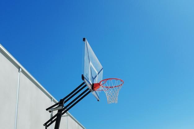 Flacher winkelschuss eines basketballkorbs unter dem schönen klaren himmel Kostenlose Fotos