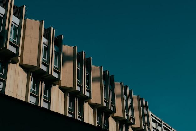Flacher winkelschuss eines braunen gebäudes mit fenstern und einem dunkelblauen himmel Kostenlose Fotos