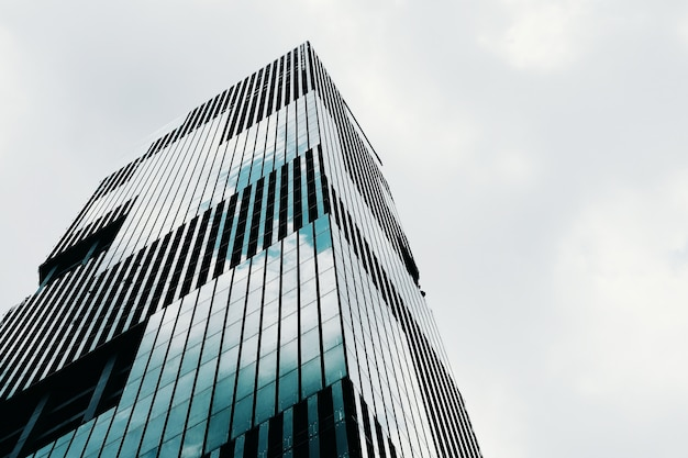 Flacher winkelschuss eines hohen modernen geschäftsgebäudes des hochhauses mit klarem himmel Kostenlose Fotos