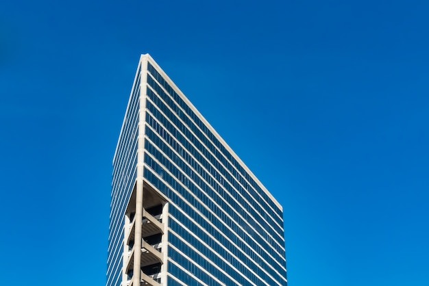Flacher winkelschuss von hohen glasgebäuden unter einem bewölkten blauen himmel Kostenlose Fotos