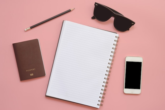 Flaches design des arbeitsplatzes schreibtisch mit leeren notizbuchbleistiftgläsern und -handy auf weinlesepastellfarbhintergrund. Premium Fotos