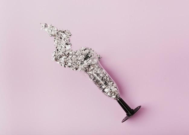 Flaches glas für champagner mit silbernen pailletten Kostenlose Fotos
