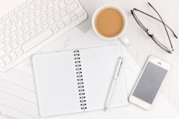 Flaches lagefoto des weißen schreibtischs mit laptop, smartphone, brillen, notizbuch und stift mit kopienraumhintergrund. attrappe, lehrmodell, simulation Premium Fotos