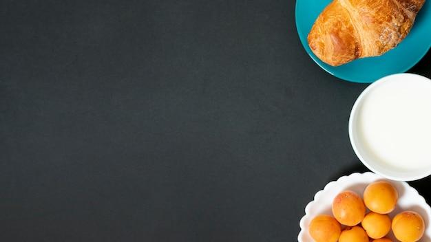 Flaches lagehörnchen, -milch und -aprikosen auf einfachem hintergrund mit kopienraum Kostenlose Fotos
