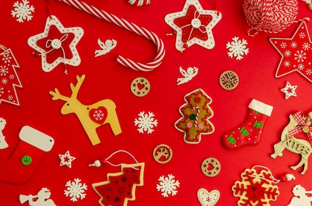 Flaches laienweihnachtsmuster aus roten weihnachtsbaumschmuck und spielzeug auf rotem grund Premium Fotos