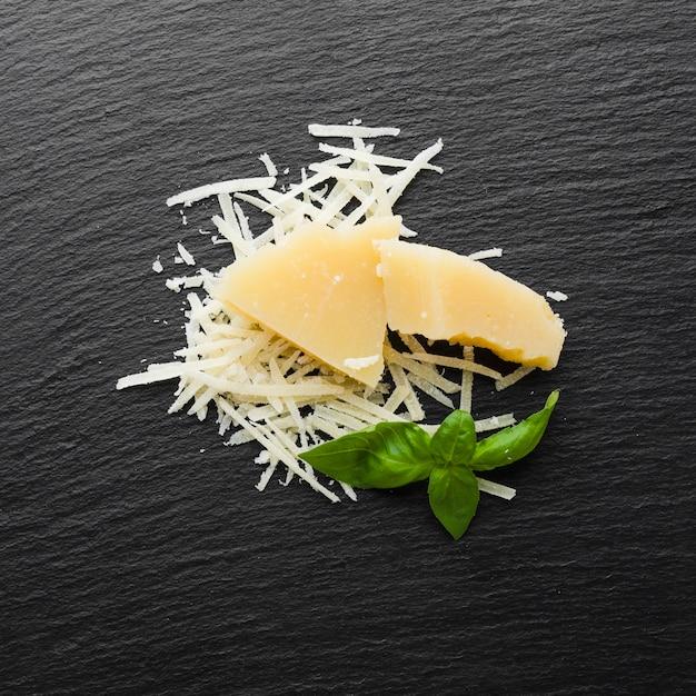 Flachlage zerriebener parmesankäse auf schwarzem hintergrund Kostenlose Fotos