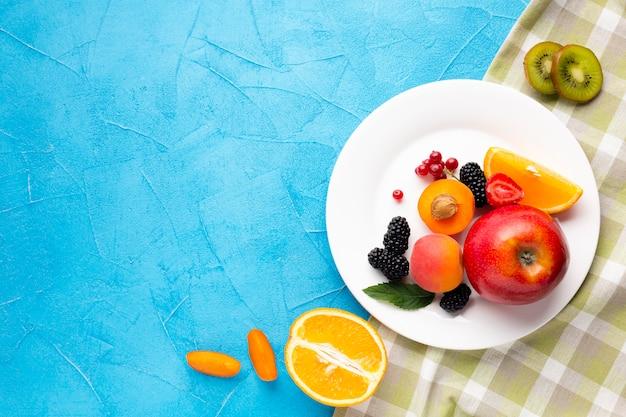 Flachlageplatte von frischen beeren und von früchten mit copyspace Kostenlose Fotos