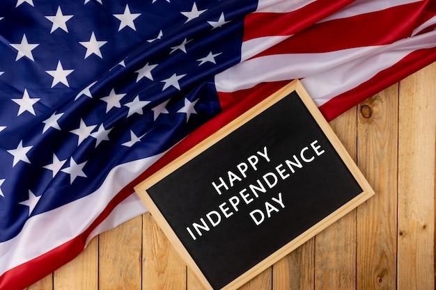 Flagge der vereinigten staaten von amerika mit tafel auf hölzernem hintergrund. Premium Fotos