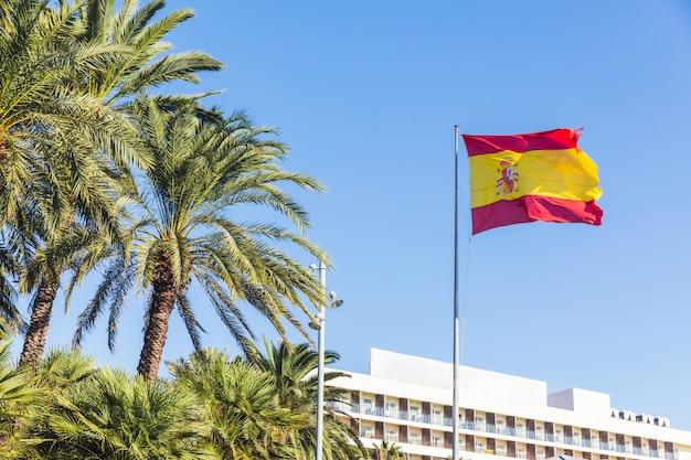 Flagge von spanien am fremdenverkehrsort mit palmen Premium Fotos
