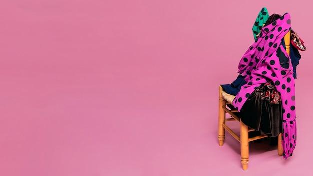 Flamencokleider auf stuhl mit rosa hintergrund Kostenlose Fotos