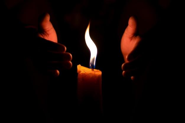 Flammenfeuer brennende kerze und zwei hände schützen windig davor Premium Fotos